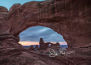 Turret arch viewed through Windows Arch in Arches National Park, Utah.