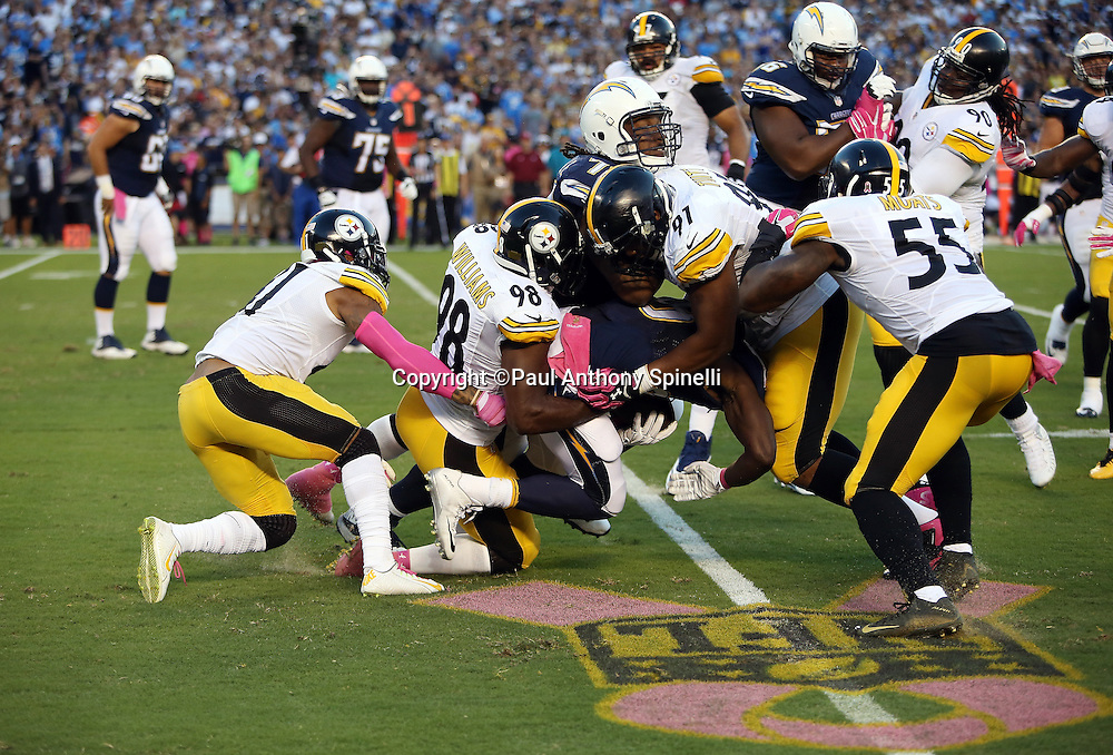 San Diego Chargers running back Melvin Gordon (28) gets gang tackled by Pittsburgh Steelers inside linebacker Vince Williams (98), Pittsburgh Steelers defensive end Stephon Tuitt (91), Pittsburgh Steelers outside linebacker Arthur Moats (55), and Pittsburgh Steelers cornerback Antwon Blake (41) on the pink, gold, and black NFL breast cancer awareness logo painted on the field grass for the 2015 NFL week 5 regular season football game against the Pittsburgh Steelers on Monday, Oct. 12, 2015 in San Diego. The Steelers won the game 24-20. (©Paul Anthony Spinelli)
