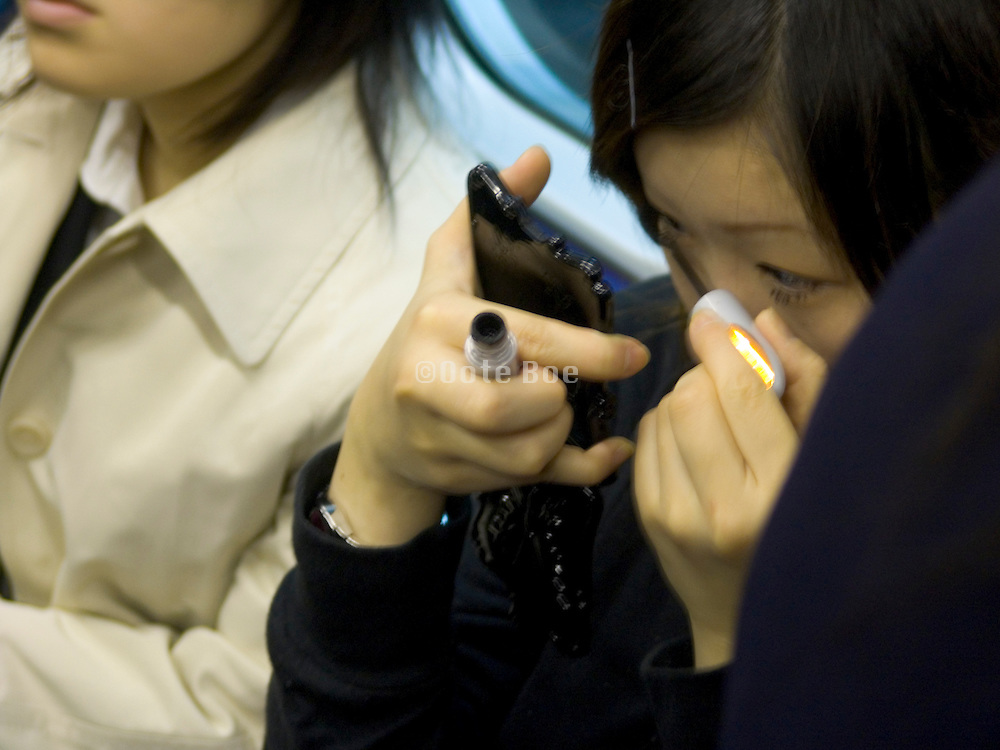 a young girl doing her eyes during her commute Japan