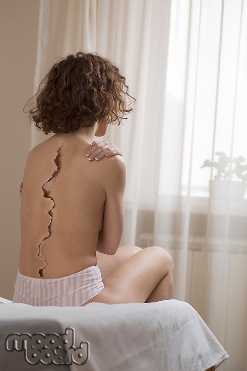 Rear view of woman with crack on back sitting in bed