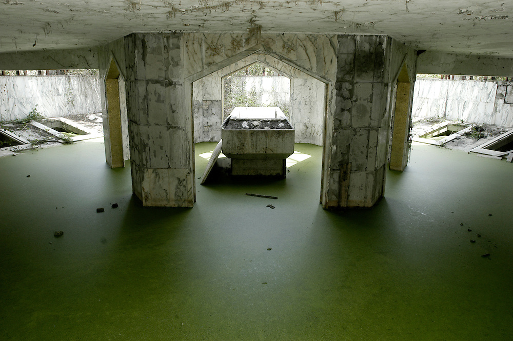 The crypt of a chapel on the grounds of the Bamboo Palace, one of the extravagant residences built by Mobutu Sese Seko and used primarily for public functions in his native village in Equateur Province. Mobutu's first wife Marie Antoinette Mobutu was buried in the central tomb and the others were reserved for his children. They were all looted during the overthrow of his rule by the forces of Laurent-Désiré Kabila..Gbadolite, DR Congo. 17/03/2009.Photo © J.B. Russell