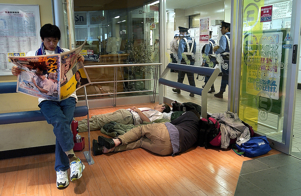 A Japanese man reads news of  England win over Denmark while English football supporters sleep off the night before at Niigata Railway Station..June 2002.©David Dare Parker/AsiaWorks Photography