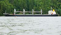 Kayaker waits while cargo ship passes on Columbia River shipping channel Oregon Washington USA.