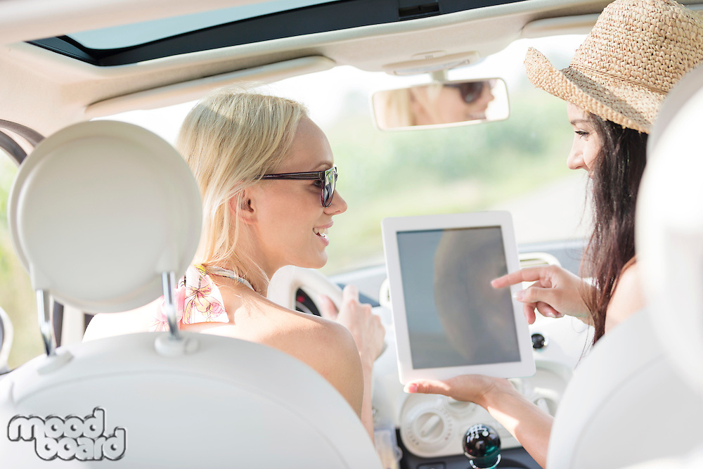 Rear view of happy women using digital tablet in car