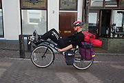 Een man rijdt met vakantiebepakking op een ligfiets.<br /> <br /> A man is riding a recumbent bike for holiday.