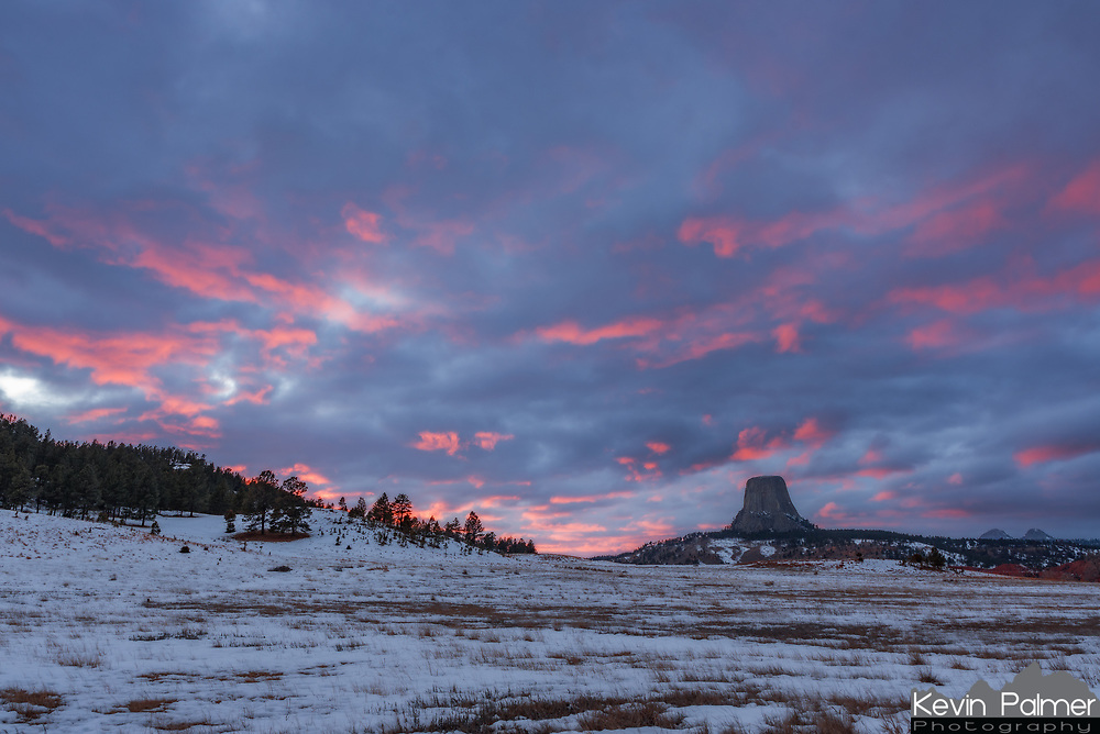 Clouds glow pink above Devils Tower at sunset just before a snowstorm moves in.