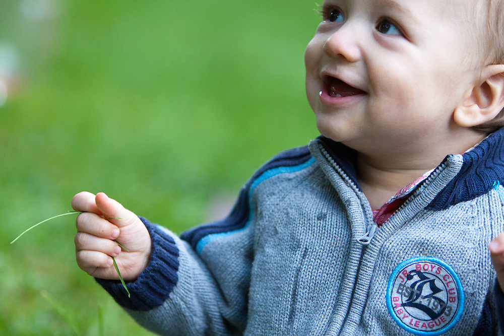 Portraits of a baby boy playing by himself and grabbing a handful of grass outside on a blanket in a grassy area.