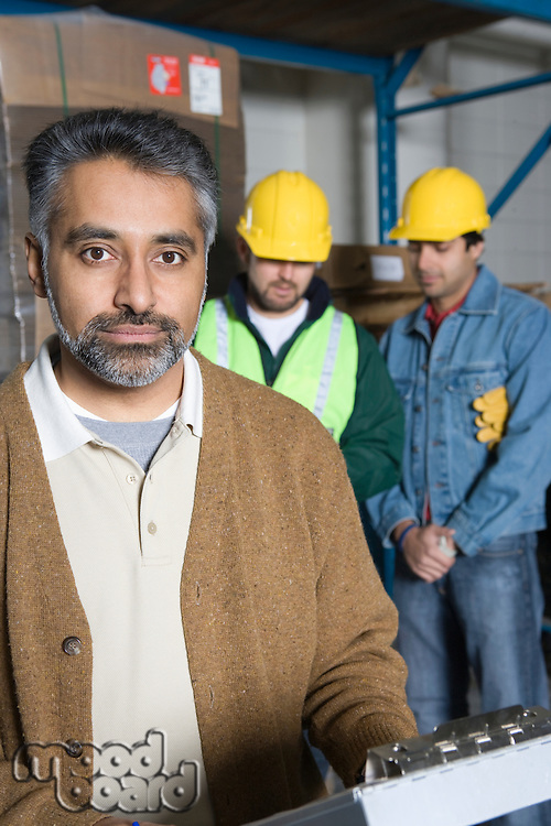 Serious men in factory colleagues in background