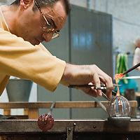 """VENICE, ITALY - DECEMBER 14:  Marino Santi, master """"maestro"""" glass maker at Eugenio Ferri & C. in Murano makes glass Christmas baubles on December 14, 2010 in Venice, Italy. The production of glass baubles is an highly skilled process,with a variety of styles, often with the inclusion of gold and silver foil."""