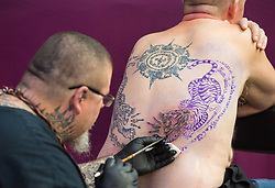 A tattoo artist works on a Japanese tattoo design during the International tattoo convention at Tobacco Dock in east London.