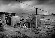 """Kichwa woman works at the entrance of her thatched-roof, partially subterranean home at a bus stop on a 4,100m (13451 ft) mountain pass below Chimborazo Volcano on the wind-swept semi-desert """"el arenal"""".  Because this mountain pass sits on the equator, it has the same cold climate all year long.  Ecuadorian Andes."""