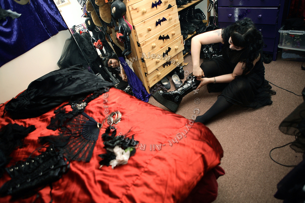 Cecile, 31, a French woman from Avignon, and one of the members in the Vampyre Connexion committee, is fitting his boots in her bedroom before a long day out with the group, on Sunday, 10 June, 2007, in Camden Town, London, England. The Vampyre Connexion is the largest and most active of all the vampire groups in the United Kingdom, counting more than 100 members that for years have gathered regularly in London to share their common love for vampires and the Dark side of life. The Connexion raised from the hashes of the Vampyre Society, the first vampire appreciation group in 1995. The group believe in the fantasy of vampires and such creatures and live it to the full. Its  roots are to be found in the legends of Bram Stokerís Dracula. The group prints its own magazine, ëDark Nightsí featuring drawings, poetry, stories, photography and events. All of the members dress very peculiar clothing, and this is a very important part of the life of the group; it is respected with pride, taste and accuracy for the detail. Most like to dress to be elegant in a range of styles from regency to Victorian, some sew their own. In addition members visit art galleries, cemeteries, churches and cathedrals, attend gigs and concerts, and hold their own parties throughout the year, Halloween being the biggest and scariest one. Membership is open to all, the only qualification: being a love of all things Vampyric.**ItalyOut**