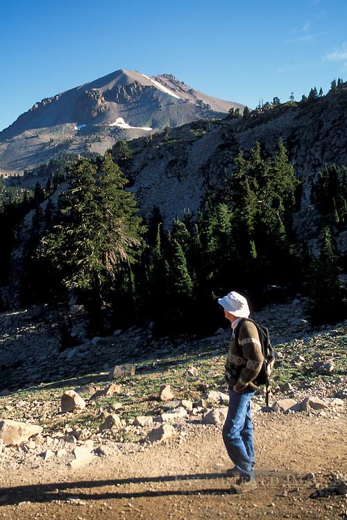 Hiker on trail to Bumpass Hell below Mount Lassen volcano peak, Lassen Volcanic National Park, California