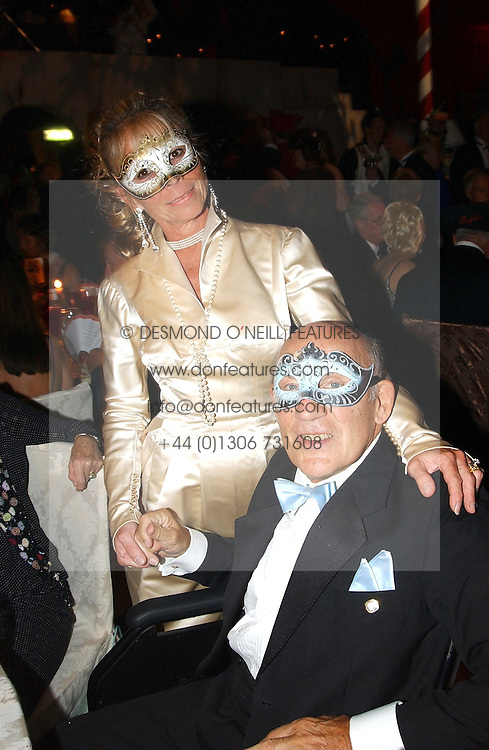 SIR STIRLING & LADY MOSS at the 2004 Goodwood Revival ball this year theme was a Venetian Masked Ball, held at Goodwood Motor Racing circuit, West Sussex on 4t September 2004.