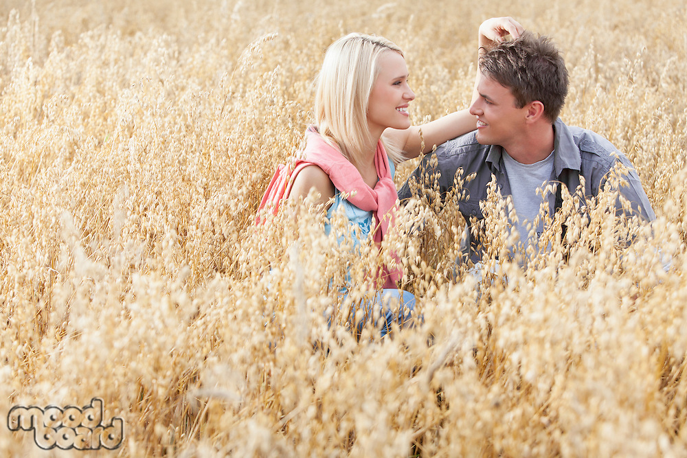 Happy loving young couple relaxing amidst field