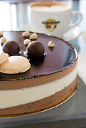 three layer chocolate cake with a cup of coffee