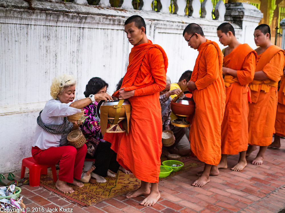 "12 MARCH 2016 - LUANG PRABANG, LAOS:  Tourists give alms to Buddhist monks during the morning tak bat in Luang Prabang. Luang Prabang was named a UNESCO World Heritage Site in 1995. The move saved the city's colonial architecture but the explosion of mass tourism has taken a toll on the city's soul. According to one recent study, a small plot of land that sold for $8,000 three years ago now goes for $120,000. Many longtime residents are selling their homes and moving to small developments around the city. The old homes are then converted to guesthouses, restaurants and spas. The city is famous for the morning ""tak bat,"" or monks' morning alms rounds. Every morning hundreds of Buddhist monks come out before dawn and walk in a silent procession through the city accepting alms from residents. Now, most of the people presenting alms to the monks are tourists, since so many Lao people have moved outside of the city center. About 50,000 people are thought to live in the Luang Prabang area, the city received more than 530,000 tourists in 2014.      PHOTO BY JACK KURTZ"