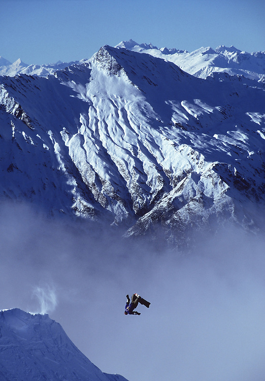 Snowboarder backflipping off a windlip against a misty mountain backdrop, Rip Curl World Heli Challenge, New Zealand