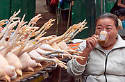 Laos. Luang Prabang. Morning market. A chicken vendor having a coffee.