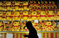A man in silhouette walk past a teddy bear on display for visitors to try play a game and win some bears during Fun Fair at Penang outside Kuala Lumpur on November 29, 2013. Picture by Mohd FIrdaus / i-Images