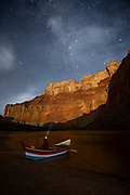 Boatman Patrick Clark takes in the majesty of the night sky from his dory, South Fork, with the moonlit canyon walls of Marble Canyon towering above him. From river mile 53 on the Colorado River at Nankoweap in Grand Canyon National Park.