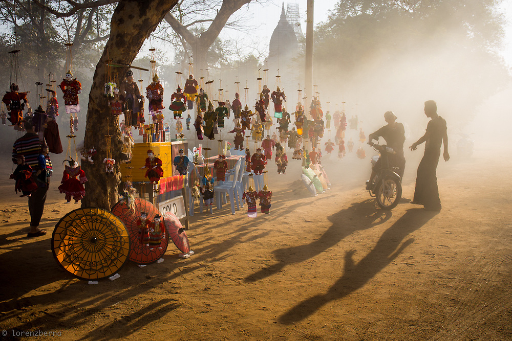 The mist of the morning envelop a Burmese Puppet stall illuminated by the first sun rays.