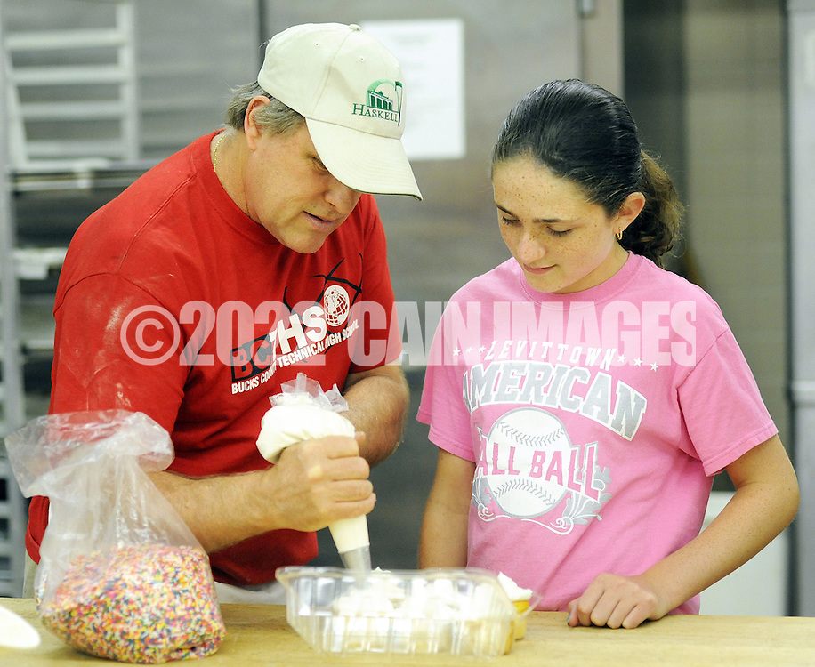 Instructor John Hose (left) shows Caitlyn Warrell, 13 of Levittown, Pennsylvania how to place icing on cupcakes during baking class Wednesday July 20, 2015 at Bucks County Technical School in Fairless Hills, Pennsylvania. (Photo by William Thomas Cain)