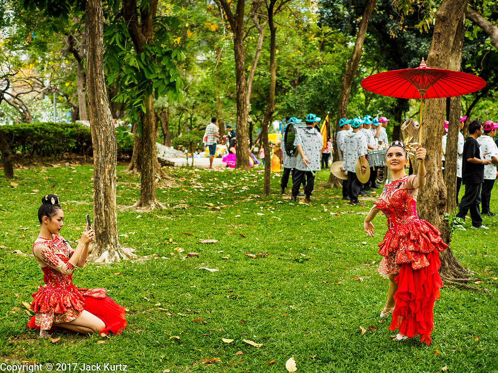 "08 APRIL 2017 - BANGKOK, THAILAND: Entertainers take photos of each other before the ""Amazing Songkran"" festival in Benchasiri Park in Bangkok. The festival was sponsored by the Tourism Authority of Thailand to highlight the cultural aspects of Songkran. Songkran is celebrated in Thailand as the traditional New Year's Day from 13 to 16 April. Songkran is in the hottest time of the year in Thailand, at the end of the dry season and provides an excuse for people to cool off in friendly water fights that take place throughout the country. Songkran has been a national holiday since 1940, when Thailand moved the first day of the year to January 1. Songkran 2017 is expected to be more subdued than Songkran usually is because Thais are still mourning the October 2016 death of revered King Bhumibol Adulyadej.       PHOTO BY JACK KURTZ"