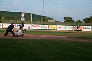 The pitcher for the Elmira Pioneers delivers a pitch towards home plate where the batter for the visiting team awaits.