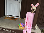 "A skeleton in a pink bunny suit with an easter basket on the front porch of a home in Kalispell, Montana. The doormat reads ""GO AWAY."""