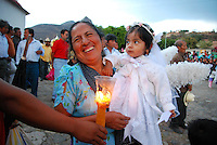 """Mexico, Oaxaca, Teotitlan del Valle, April 18, 2011. On a moody Monday in southern Mexico, the Zapotec townspeople of Oaxaca's Teotitlan del Valle reenact all fourteen Stations of the Cross through this mountain community's winding cobblestone streets. From the first station, where Jesus is condemned to die, to the last, where he is laid in his tomb, somber processions accompanied by flowers, singers and a brass band stop at each refuge, adorned with """"tapetes"""" created by master carpet weavers and blessed with food and drink for all."""
