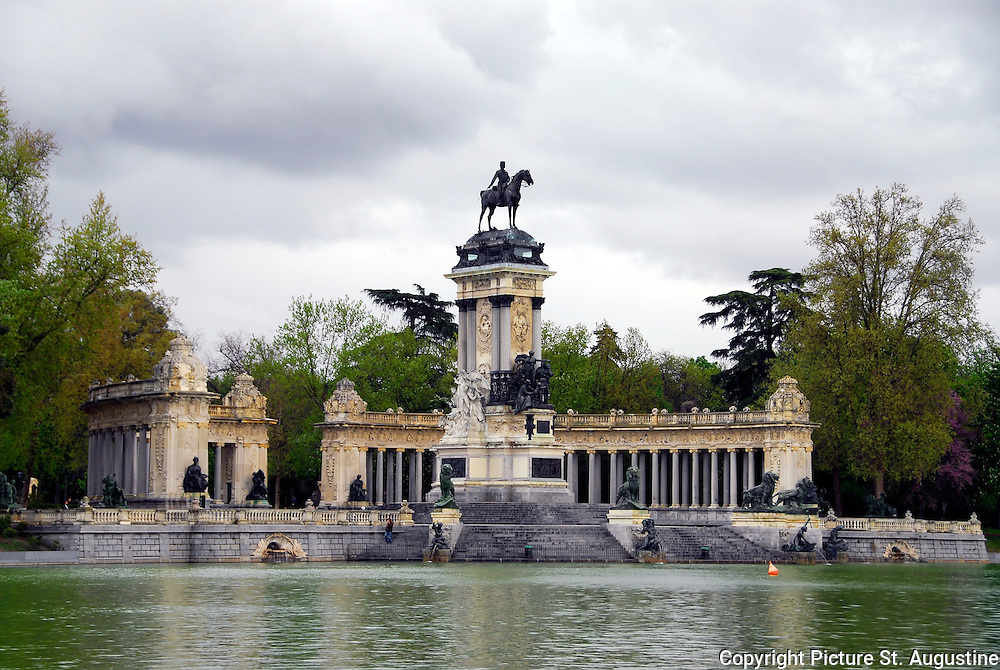 "A rainy spring day in the park. Everything looks clean and refreshed between showers in the Park Retiro, Madrid, Spain. The  ""Estanque del Retiro"" is a large man made lake that is one of the centerpieces of the Park. This lake is a wonderful place to rent a row boat and glide past the semi circular colonnade monument to King Alfonso XII. The monument was built in 1922 by King Alfonso XII's mother. A large equestrian statue of the King anchors the monument."