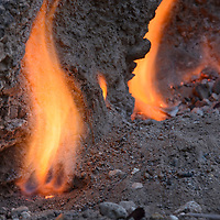 Eerie smokeless fires dance among fissures in the limestone rocks where ignited natural gas escapes in Tanjung Api (Fire Cape) National Park. Central Sulawesi, Indonesia.
