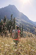 A young woman hikes through an overgrown field into the sunlight on the swiftcurrent pass trail in Glacier National Park, Montana.