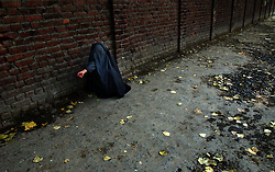 A women dressed in a burqua begs for money in  Srinagar, the summer capital of the state of Kashmir and Jammu, November 8, 2001.  Many women are afraid to go outside without a full veil after an unknown organization declared that acid would be thrown on their face if they walked outside uncovered.