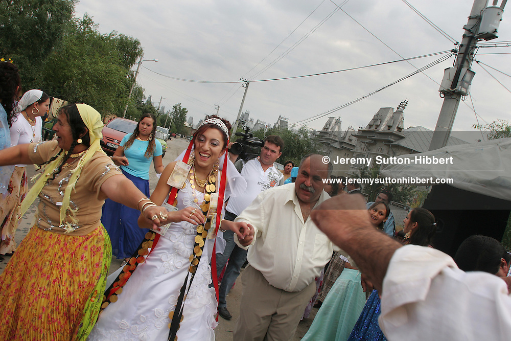14 year old roma (gypsy) bride Garoafa Mihai dances in the street with her dowry of gold coins, assisted by her new father and mother-in-law, in Sintesti, Romania, on Sunday, Sept. 24th 2006. Day two of the wedding between Garoafa Mihai, aged 14, and Florin 'Ciprian' Lulu, aged 13, Roma (gypsies) from the village of Sintesti,15 kilometres from Bucharest, Romania. Their partnership was decided by their parents and not through love, and under Romanian law is illegal. The children will neither complete legal paperwork for the wedding, nor visit the local Romanian Orthodox church for a blessing. On her wedding day Garoafa wore approximately 30-40,000 USD of gold Franz Josef coins on her dress, part of the large dowry that she takes with her as she begins her married life. For the guests and for the people of the village another 30,000 USD of pigs, approximately 100,  were killed to be eaten and given away as presents of food. Another 30,000 USD was spent on famous Roma musicians to come and sing 'manele'  type music at the wedding extolling the wealth and status of their patrons for the weekend in their songs.