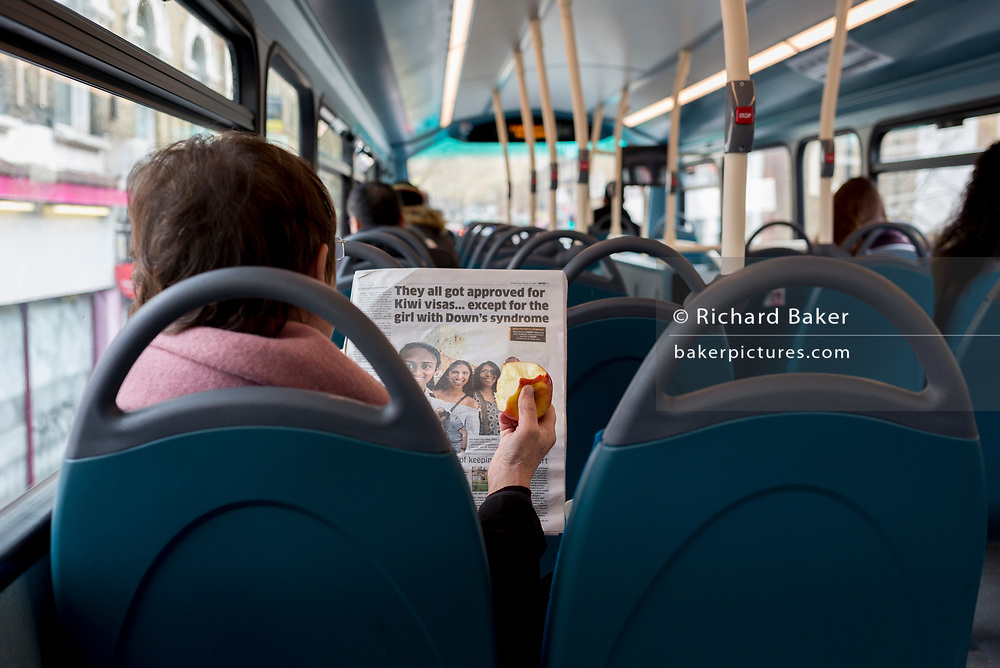 A lady passenger reads a copy of a newspaper while eating an apple, on a bus in south London, on 27th March 2019, in London, England