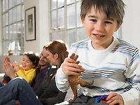 Boy (3-6) holding toy dinosaur in living room (portrait)