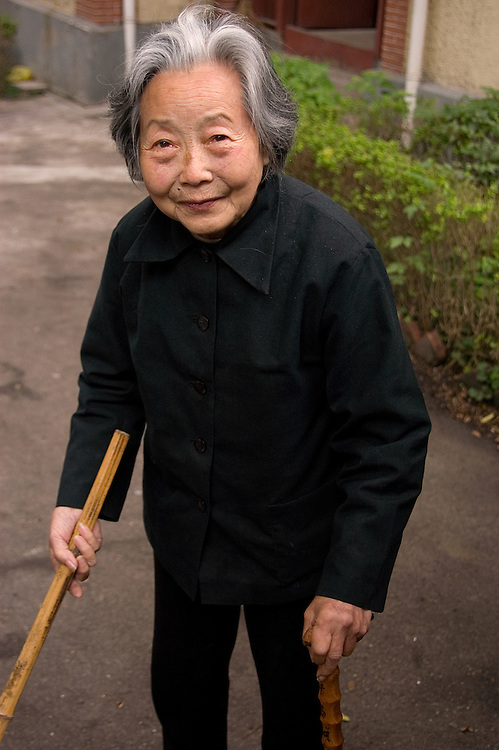 Even though she needs a cane to help her walk, this lady sweeps her entire property by herself