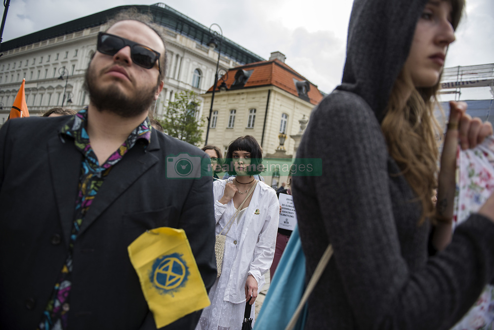 May 23, 2019 - Warsaw, Mazowieckie, Poland - Activists from Extinction Rebellion seen listening to a speech in front of the presidential palace during the protest..A protest was organized in Warsaw by the Extinction Rebellion movement and the Youth Strike for Climate against the passivity of the Polish authorities regarding the oncoming climate disaster and the great extinction of animal species..Dozens of people in black sacks layed on the sidewalk in front of the Presidential Palace. They also brought a black coffin as a symbol of the future of humanity. (Credit Image: © Attila Husejnow/SOPA Images via ZUMA Wire)