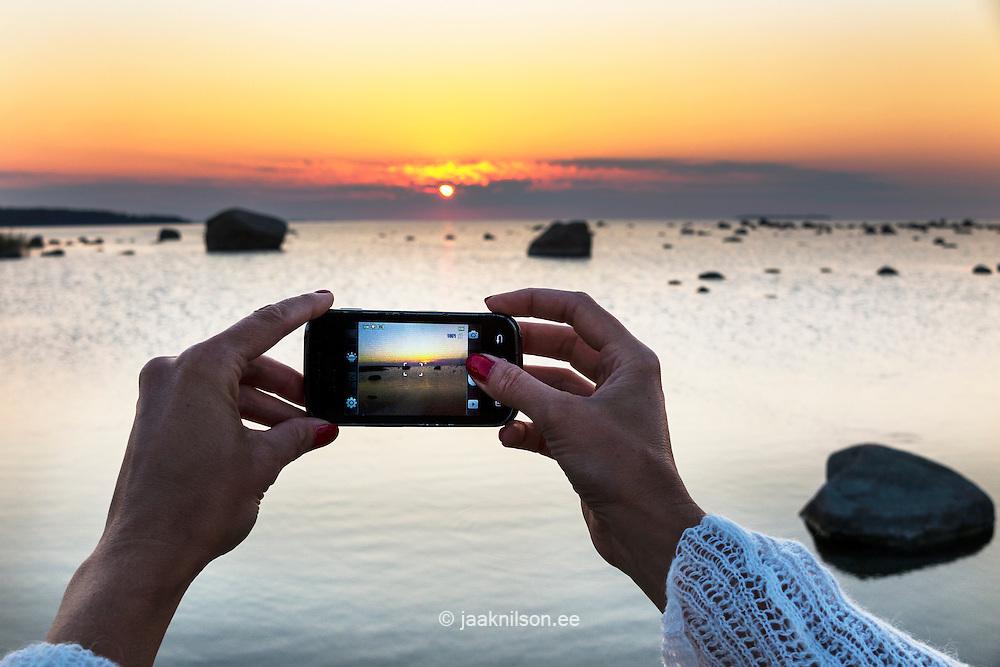 Woman hands holding camera phone.  Sunset at Käsmu beach in Estonia.