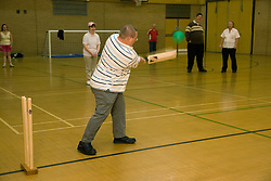 Group of Day service users with learning disability playing indoor cricket in the gym,