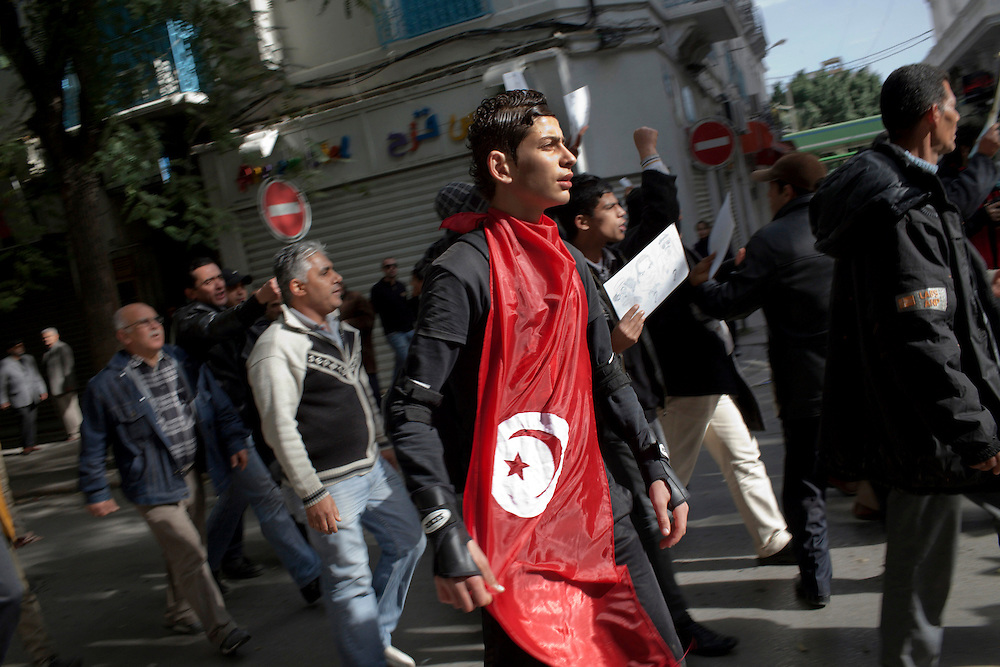 A boy wears a Tunisian flag during a demonstration demanding the dissolution of the new interim governement...On 17 december Mohamed Bouazizi a fruit seller form the city of Sidibouzid in Tunisia set fire to himself starting a wave of protest that will change several arab countries under the name of Arab Spring..Despite the dictator Zine El-Abidine Ben Ali left the country on 14 January after weeks of protest the demonstrations continue asking for the political party of the regime (RCD) and all the political men involved on the past government where banned from the political life ..
