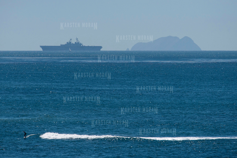 March 19, 2018 - San Diego, Calif. : A U.S. Navy aircraft carrier rounds Point Loma on its way to Navy Base San Diego. The Coronado Islands can be seen in the distance. A surfer and sailboat can be seen in the foreground. CREDIT: Karsten Moran / Redux