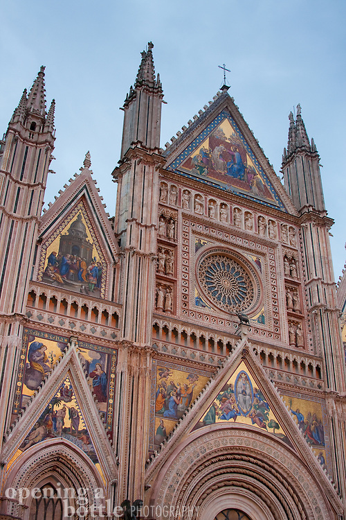 The Duomo di Orvieto at dusk, with its gilded facade illuminated against a cloudy blue sky. Orvieto, Umbria, Italy.