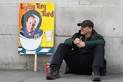 "London, April 16th 2016. A man sits in front of the national gallery next to a discarded placard after thousands of people supported by trade unions and other rights organisations demonstrate against the policies of the Tory government, including austerity and perceived favouring of ""the rich"" over ""the poor""."