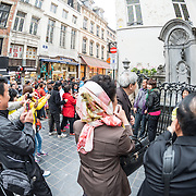 Crowds of tourists taking photos in front of the Mannekin Pis, a small bronze fountain sculpture of a naked little boy urinating into the fountain. Installed in about 1619 by Hiëronymus Duquesnoy the Elder, it is a cultural symbol of the city of Brussels and a famous tourism landmark.