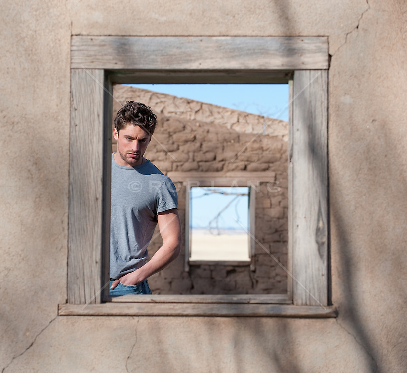 Guy in a tee shirt looking out an adobe window