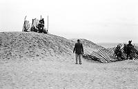 Elderly man watches children play on the beach, Brooklyn, New York, NY