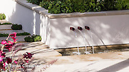 Detail of water feature set into white plaster wall with three red metal cascades dropping into a rill